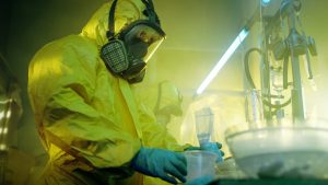 man in chemical suit cleaning lab